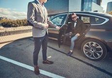 Den attraktiva mannen i solglas?gon talar vid smartphonen och sitter i bilen, medan hans assistent ?r den ?ppnande d?rren f?r hon arkivbilder