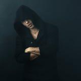 Den attraktiva mannen i svart hoodie korsade hans armar Arkivfoto