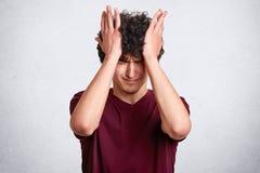 Den attraktiva mannen med lockigt hår, bär den tillfälliga rödbruna t-skjortan, har olyckliga expresions, trycker på hans huvud m arkivfoto