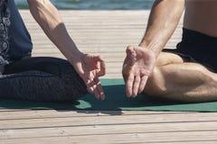 Den attraktiva mannen och kvinnlig praktiserande yoga i lotusblomma poserar slut upp händer Ett ungt par som gör yoga för att med royaltyfria foton