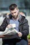 Den attraktiva mannen sitter i en coffee shop som läser nyheternapapperet royaltyfri fotografi