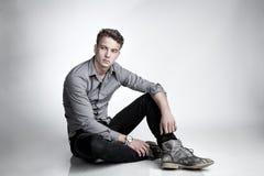 Den attraktiva mannen sitter på golvet Arkivfoton