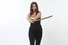 Den attraktiva medelåldersa kvinnan i sportar utrustar att rymma en bokken eller ett träsvärd Arkivbild