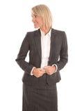 Den attraktiva mitt åldrades affärskvinnan som från sidan ser för att smsa royaltyfri bild