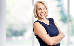 Den attraktiva mitt åldrades kvinnan med ett härligt leende nära fönstret royaltyfri fotografi