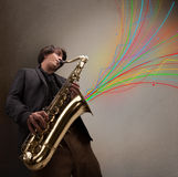 Den attraktiva musiker som leker på saxofon, fördriver den färgrika abstrakt begrepp Arkivbilder