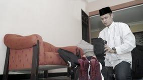 Den attraktiva muslim asiatiska mannen f?rbereder bagageresv?skan arkivbilder