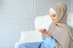 Den attraktiva muslim kvinnan i hijab bl?ddrar internetsidor i smartphonen som sitter p? soffan royaltyfri bild