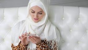 Den attraktiva muslim kvinnan i hijab bl?ddrar internetsidor i smartphonen som sitter p? soffan arkivfilmer
