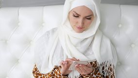 Den attraktiva muslim kvinnan i hijab bl?ddrar internetsidor i smartphonen som sitter p? soffan stock video