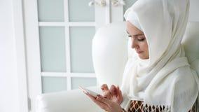 Den attraktiva muslim kvinnan i hijab bl?ddrar internetsidor i smartphonen som sitter p? soffan lager videofilmer