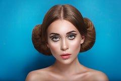 Den attraktiva mystiska unga kvinnan med den dubbla hårbullen i frisyr för prinsessa Leia ser in mot kameran Royaltyfri Foto