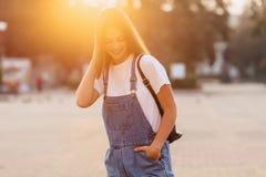 Den attraktiva nätta flickan med portföljen går på gatan på morgonen royaltyfria foton