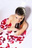 Den attraktiva nakna flickan tycker om ett exponeringsglas av vin i bad med mjölkar Royaltyfria Bilder