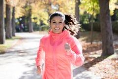 Den attraktiva och lyckliga löparekvinnan i höstsportswearspring och utbildning på att jogga utomhus genomkörare i stad parkerar Fotografering för Bildbyråer