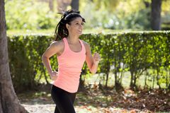 Den attraktiva och lyckliga löparekvinnan i höstsportswearspring och utbildning på att jogga utomhus genomkörare i stad parkerar Royaltyfri Foto