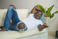 Den attraktiva och lyckliga svarta afrikansk amerikanmannen kopplade av den hemmastadda soffasoffan som tycker om hålla ögonen på arkivfoto