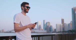 Den attraktiva och stiliga unga mannen med h?rligt leende och millennial utveckling z f?r hipster ser, bl?ddrar till och med soci stock video