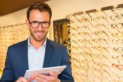 Den attraktiva optiker som arbetar med minnestavlan i hans exponeringsglas, shoppar arkivfoton