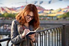 Den attraktiva rödhåriga flickan organiserar feriehändelser som tänker th Royaltyfri Foto