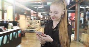 Den attraktiva rödhåriga kvinnan läser ett meddelande på en mobiltelefon stock video