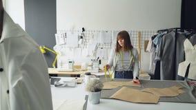 Den attraktiva sömmerskan mäter pappers- mallar för kläder som ligger på studiotabellen med mått-bandet Kvinnan är lugna och lager videofilmer