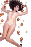 Den attraktiva sexiga kvinnan med den guld- bikinin för sken som ligger, jul klumpa ihop sig runt om henne Arkivbilder
