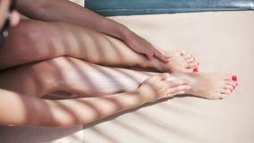 Den attraktiva sexiga kvinnan sunbed på nära pölen som applicerar lotion för solkvarter på hennes kropp lager videofilmer