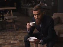 Den attraktiva skäggiga affärsmannen tycker om varmt kaffe royaltyfri foto