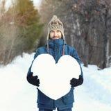 Den attraktiva skäggiga mannen som rymmer en enorm hjärta gjord av snö och att stå på den snöig vägen i vinter, parkerar for för  arkivfoton