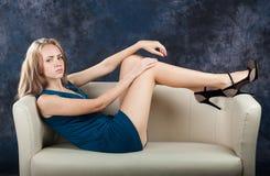 Den attraktiva spensliga flickan ligger på soffan Arkivbilder