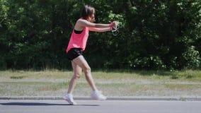 Den attraktiva sportive flickadansen parkerar in Ung flicka som utför löjlig dans och omkring bedrar Gullig flicka i rosa skjorta stock video