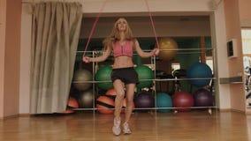 Den attraktiva sportive kvinnan med det magra diagramet hoppar over hopprepet på idrottshallen 4K arkivfilmer