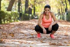 Den attraktiva sportkvinnan i löparesportswearen som tar ett avbrott, tröttade att le som var lyckligt och som var gladlynt efter royaltyfria foton