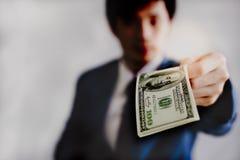 Den attraktiva stiliga unga affärsmannen ger pengar eller dollar arkivfoto