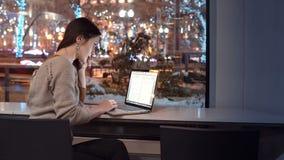Den attraktiva unga affärskvinnan som arbetar på bärbar datorsammanträde på stången, den utvändiga vinternattstaden, dekorerade f royaltyfria bilder