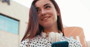 Den attraktiva unga brunetten med charmigt leende är bläddra och smsa via mobiltelefonen Upp närbildståenden 4K stock video