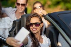 Den attraktiva unga brunettkvinnan i iklädd solglasögon en vit t-skjorta sitter med vänner i en svart cabriolet gör arkivbilder