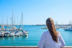 Den attraktiva unga Caucasian kvinnan med långa ställningar för den hårBoho tunikan på stranden ser yachtsegelbåtar som förtöjas  royaltyfri bild