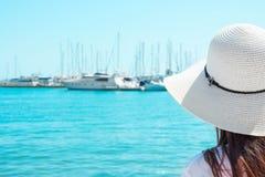 Den attraktiva unga Caucasian kvinnan med långt hår i hattställningar på stranden ser yachtsegelbåtar som förtöjas i marina arkivfoto