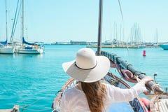 Den attraktiva unga Caucasian kvinnan med långt hår i hattställningar i tappningsegelbåt ser yachter som förtöjas i marina arkivfoton