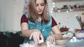 Den attraktiva unga Caucasian kvinnan spenderar tid bak en idérik hobby flickan hugger entusiastiskt en platta av lera arkivfilmer