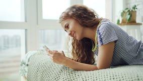 Den attraktiva unga damen använder smartphonen som ligger på den hemmastadda rörande skärmen för säng och att le Härlig lägenhet  arkivfilmer