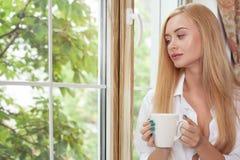 Den attraktiva unga flickan är avslappnande med den varma drinken Arkivbilder