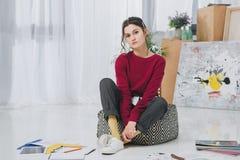 Den attraktiva unga flickan bland skissar Arkivfoto