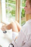 Den attraktiva unga flickan drömmer nära ett fönster Arkivbild