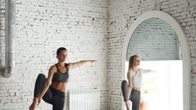 Den attraktiva unga flickan har individuell yogaövning med den yrkesmässiga instruktören och gör att stå balansera arkivfilmer
