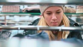 Den attraktiva unga flickan i en hatt väljer kläder i shoppar arkivfilmer