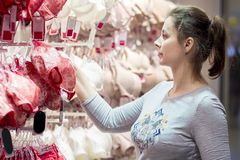 Den attraktiva unga flickan i en underkläder shoppar väljer behån Den nätta trevliga kvinnan i modeboutique köper underkläderna royaltyfria foton