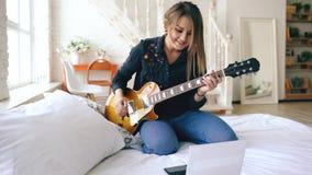Den attraktiva unga flickan som lär att spela den elektriska gitarren med anteckningsboken, sitter på säng i sovrum hemma royaltyfri foto